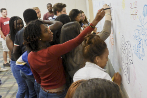 Temple University students draw on large paper as part of creativity training