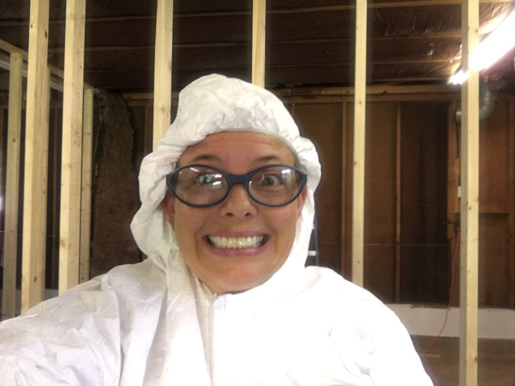 Amy in a Tyvek suit and safety glasses