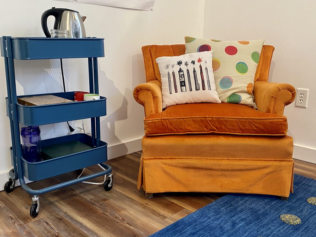 Amy's orange comfy chair with 2 pillows